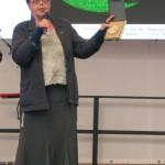 Kuratorin Gabriele Stolze zeigt die Gedenkmünze an die Ausstellung für die Künstler